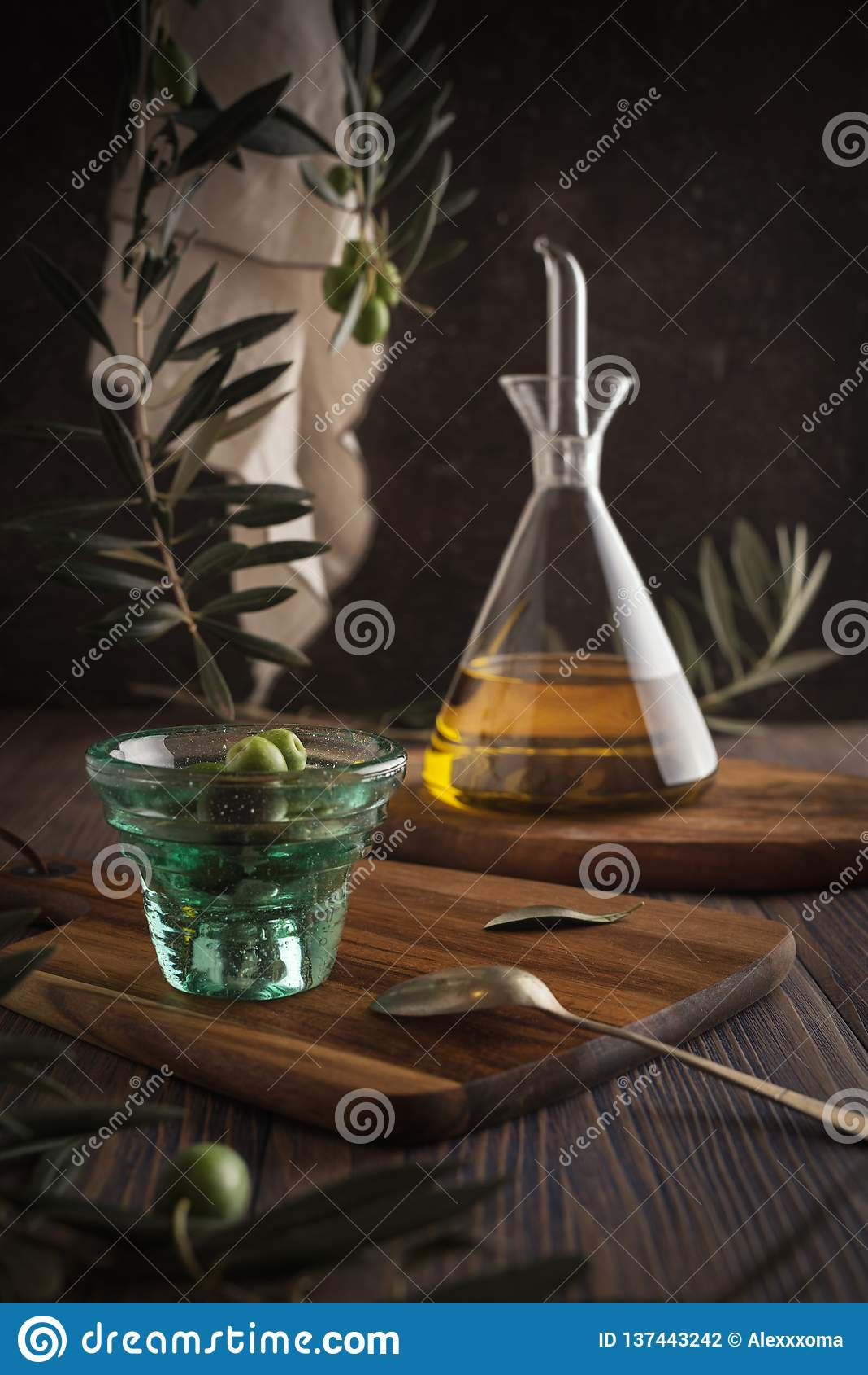 Extra jungfrulig olivolja i glasflaska med koppen av oliv på lantlig bakgrund eyes den härliga kameran för konst mode som fulla k