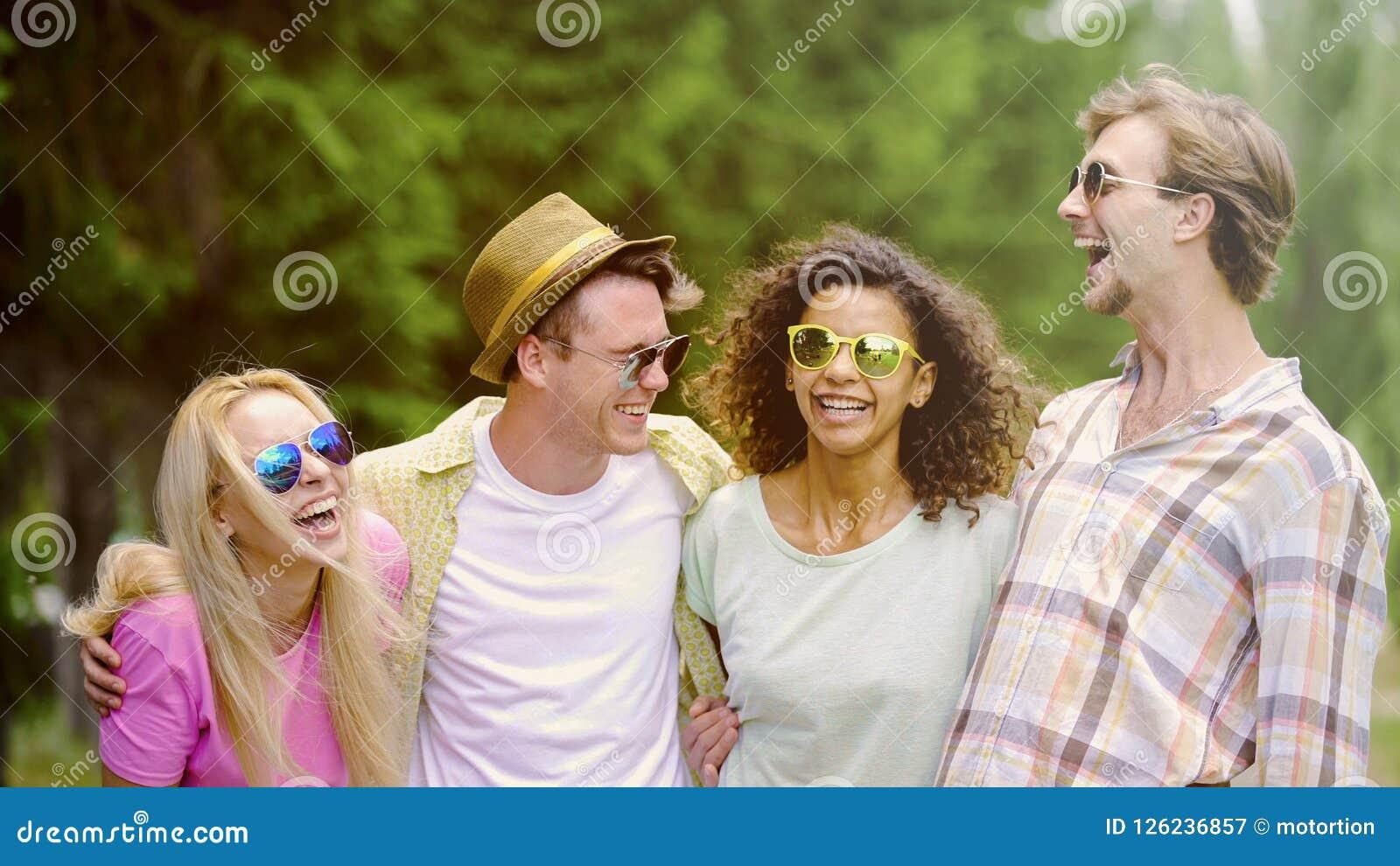 Extrem glückliche junge Leute, die über Witz, enge Freunde draußen sich treffen lachen