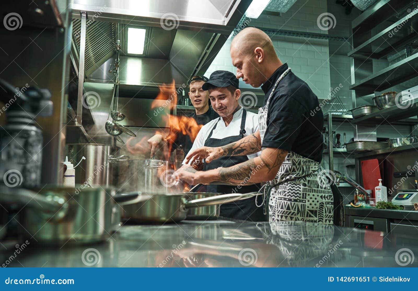 Extrem matlagning Profesional kock som undervisar hans två unga deltagare i utbildning hur hur till flambemat säkert Restaurangkö