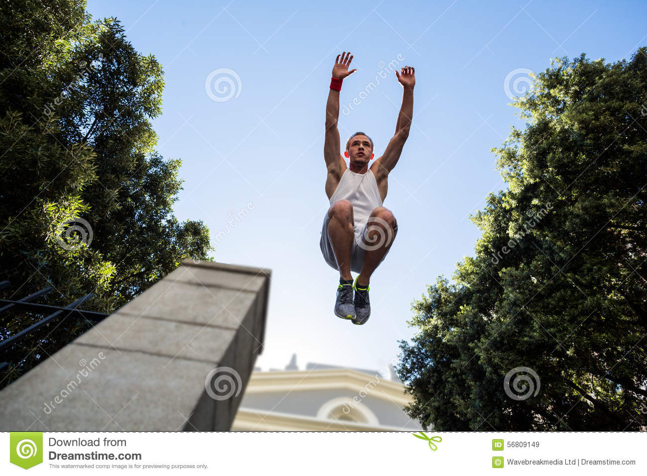 extreme athlete jumping in the air in front of a building stock