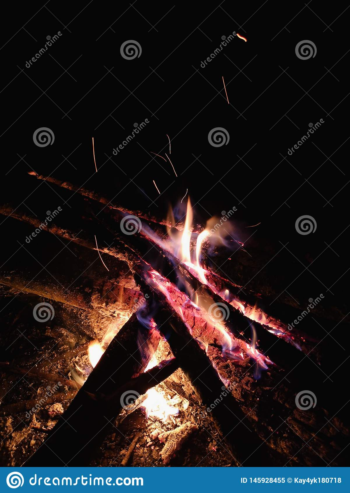 Extreme close up of fire sparks moving on dark night sky as black background coming from brightly burning warm outdoors