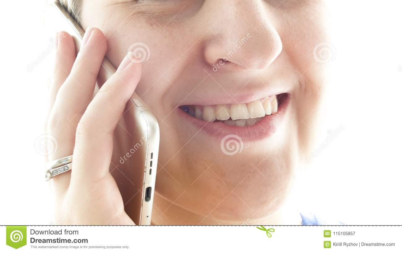 Extreme closeup photo of young smiling woman talking by mobile phone