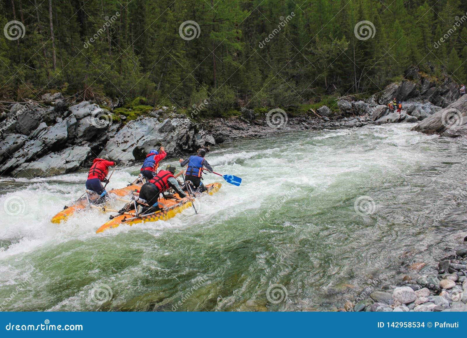 Extreme sportsmen go through the difficult turbine rapid on a catamaran