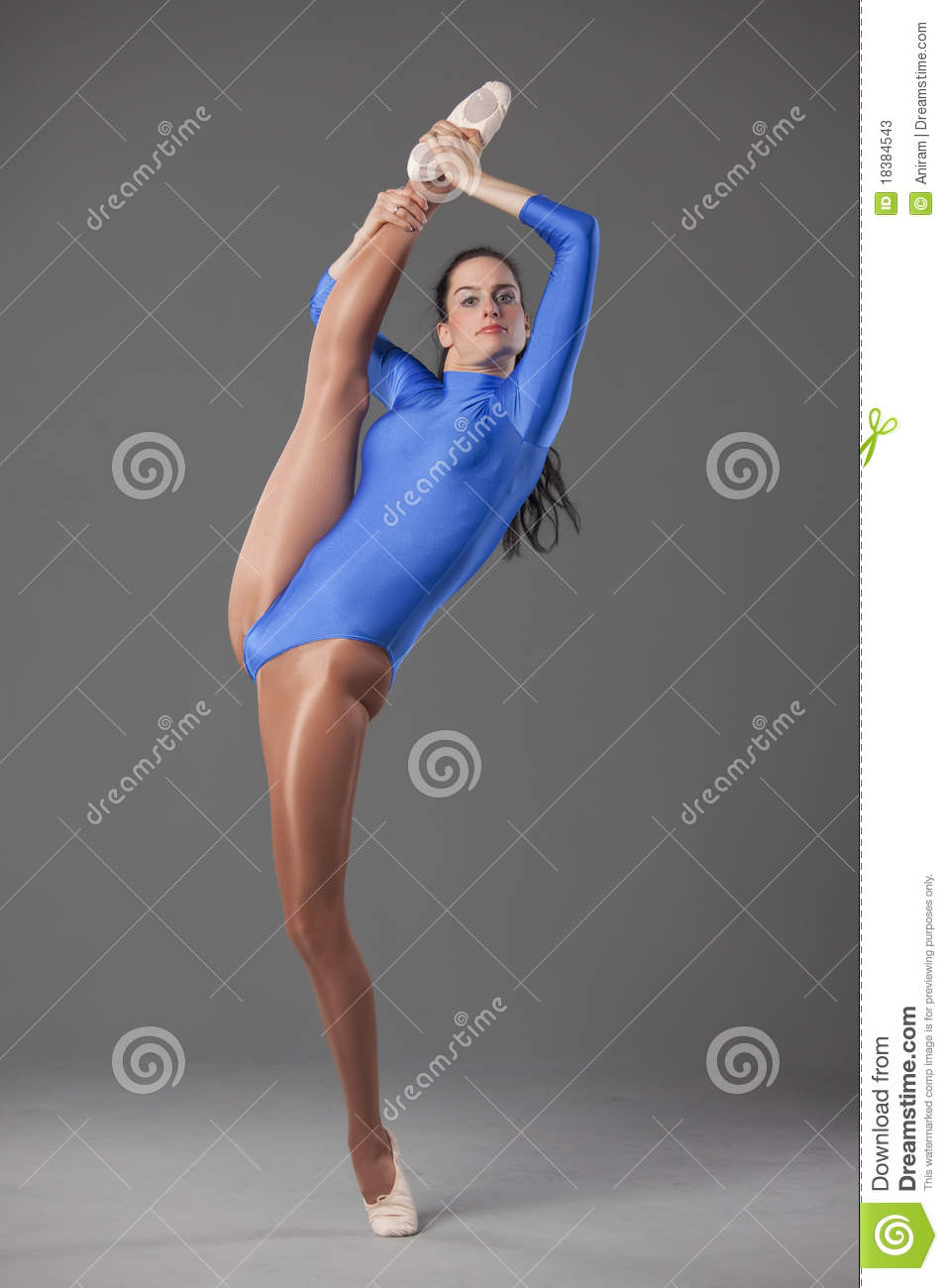 Female gymnast in extreme splits pose over grey background.