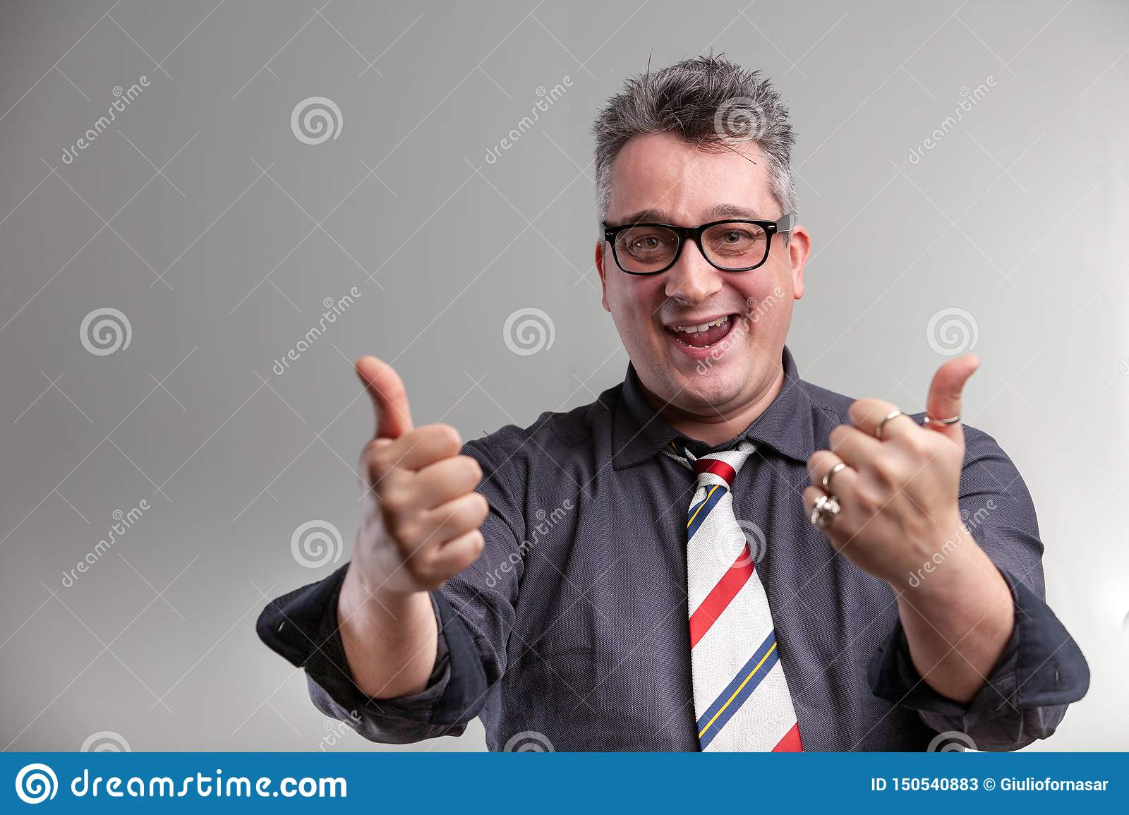 Exultant businessman giving a double thumbs up