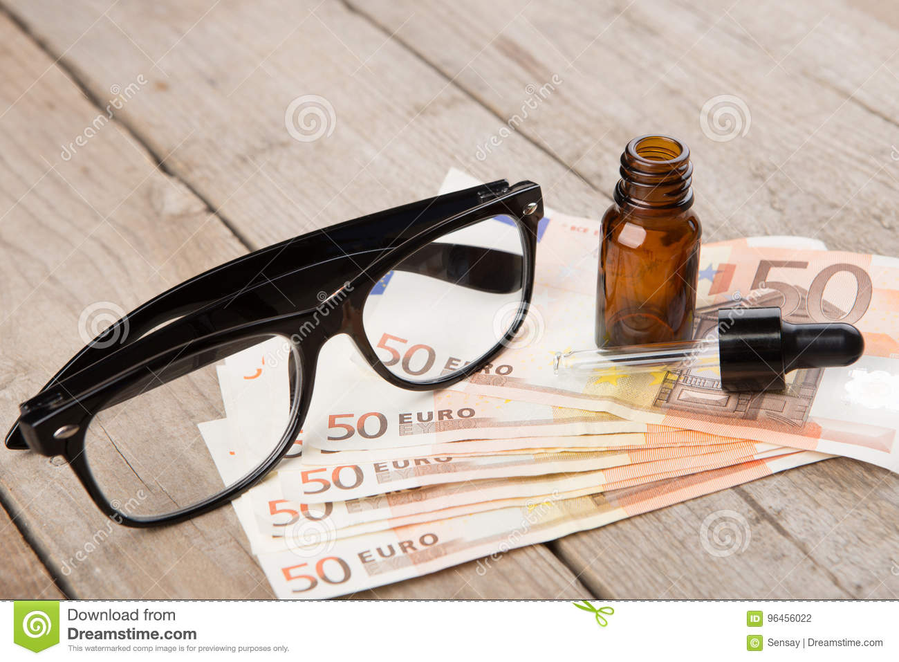eye care concept - reading glasses, eye drops and money stock photo