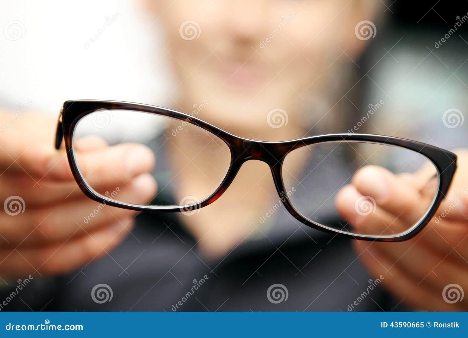 Eyeglasses λαβής χεριών γυναικών μπροστά από την