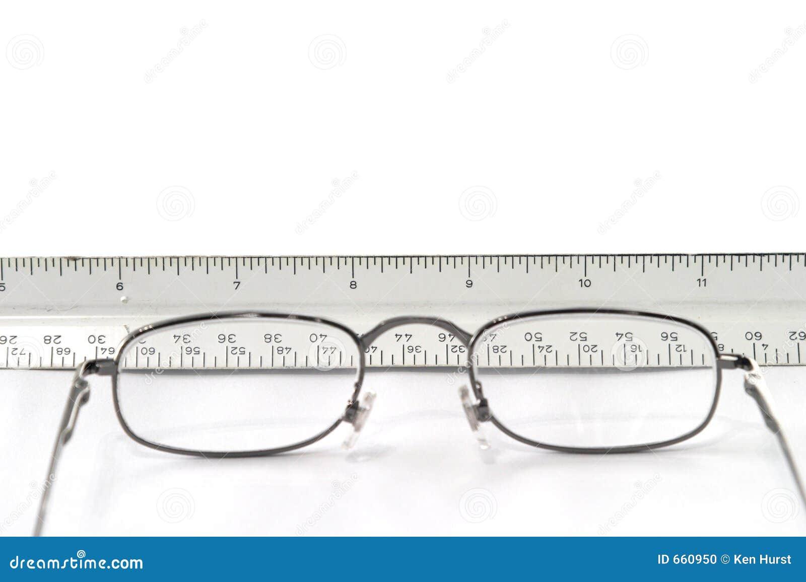 Eyeglasses da leitura na tabela com vista da régua através dos vidros