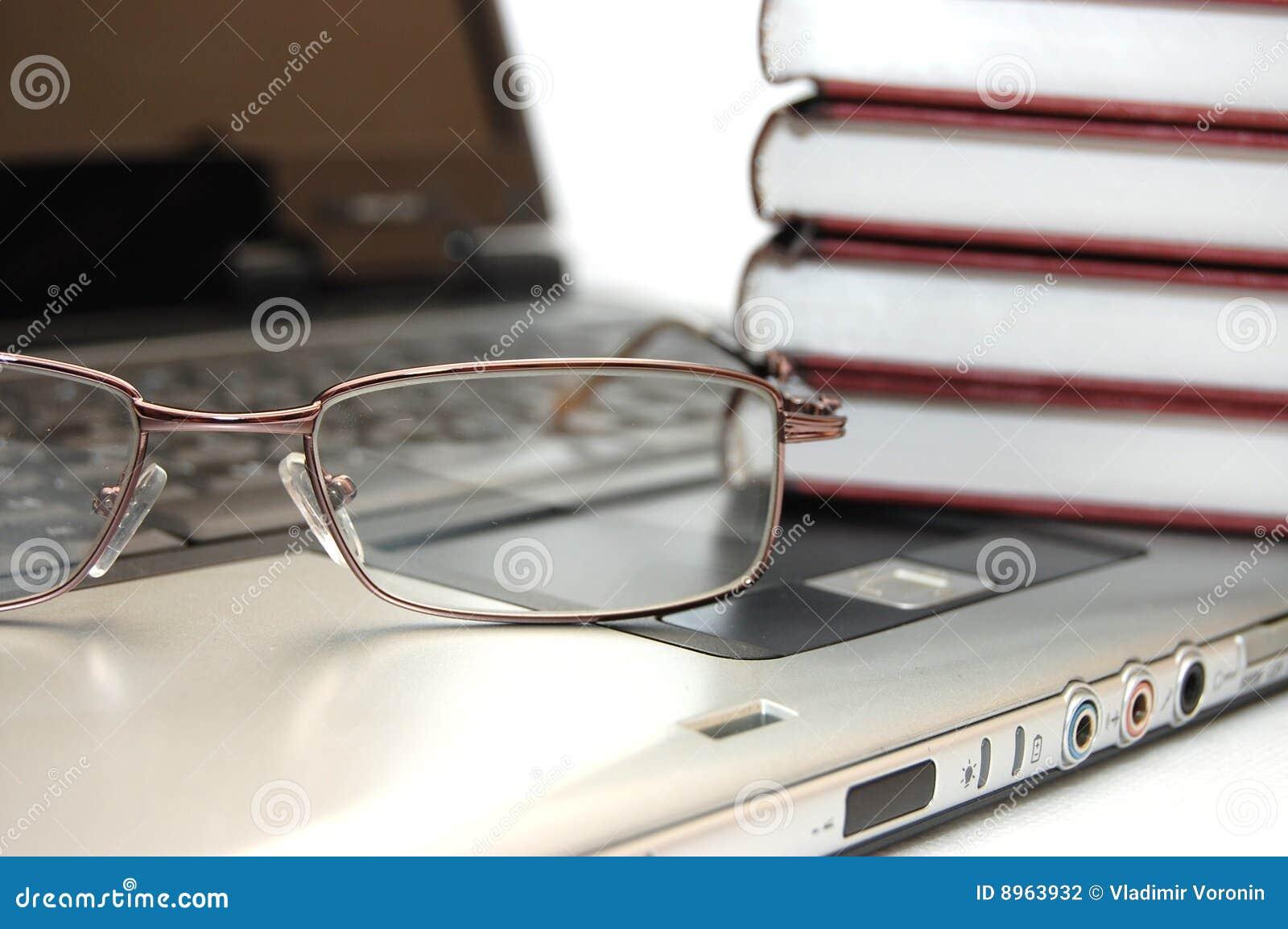 Eyeglasses e livros no portátil