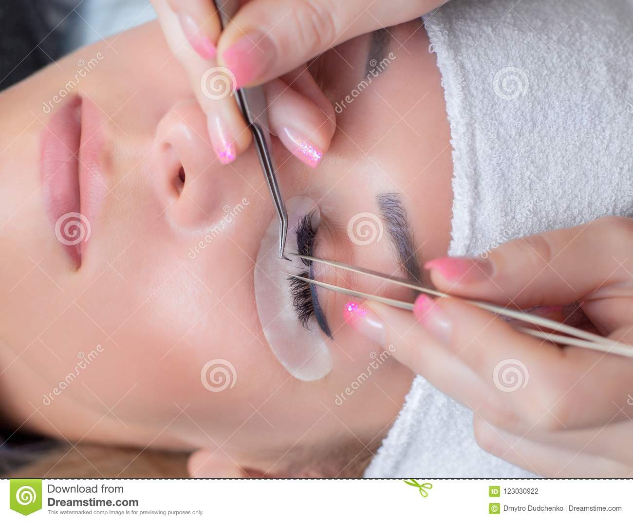 Eyelash extension procedure close up. Beautiful Woman with long lashes