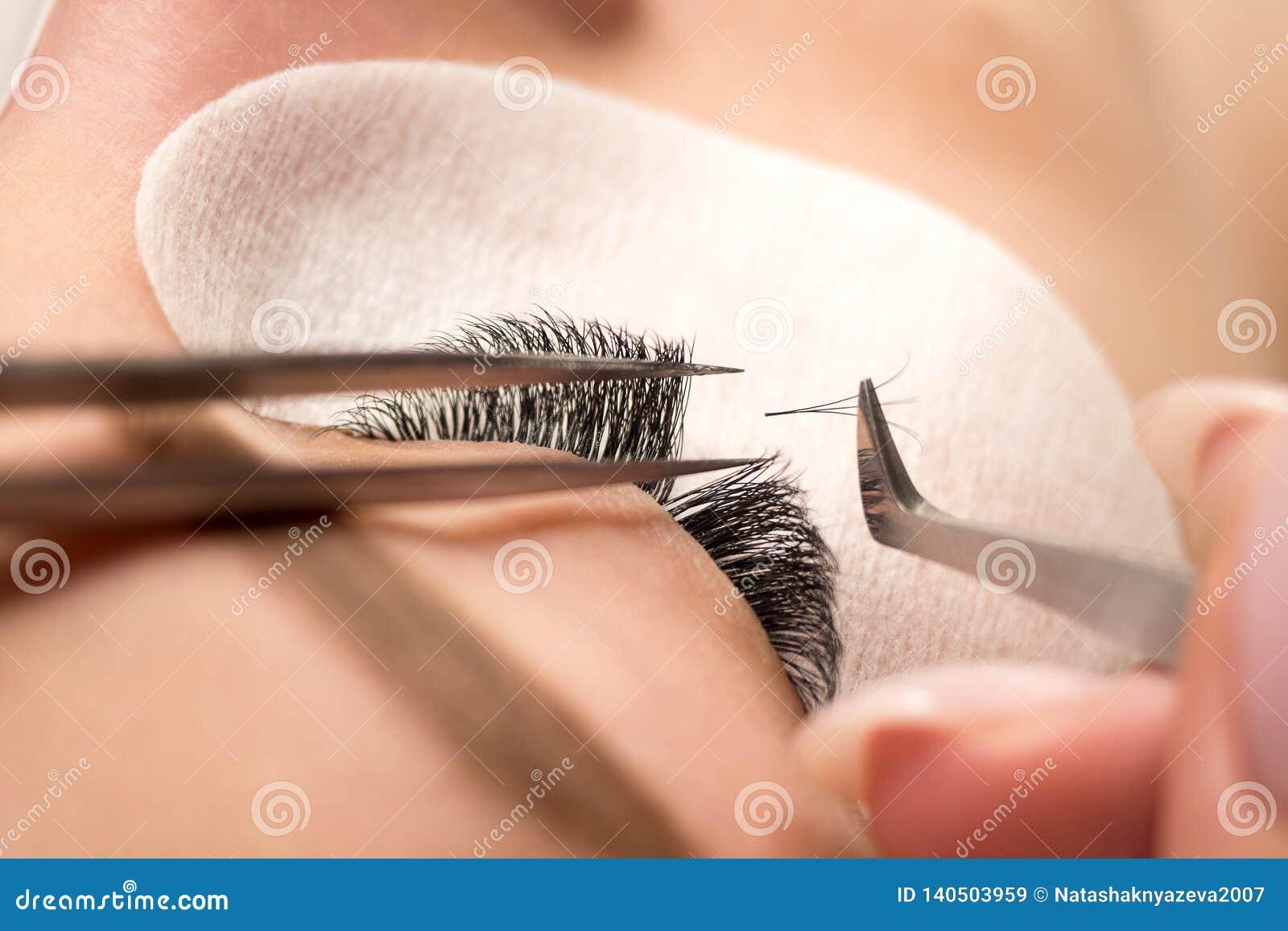 Eyelash extension procedure. Female eye with long black eyelashes, close up, selective focus.