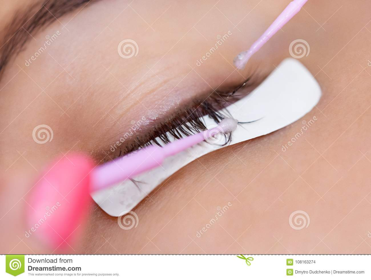 Eyelash removal procedure close up. Beautiful Woman with long lashes in a beauty salon.