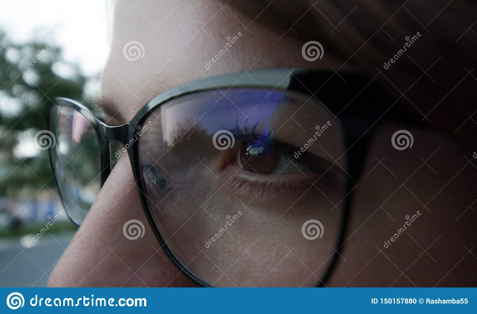 eyes of the girl wearing glasses in a black frame