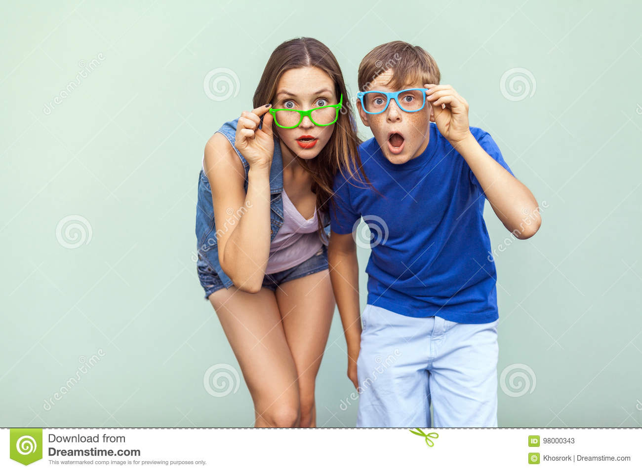 Eyewear concept. WOW faces. Young sister and brother with freckles on their faces, wearing trendy glasses, posing over light green