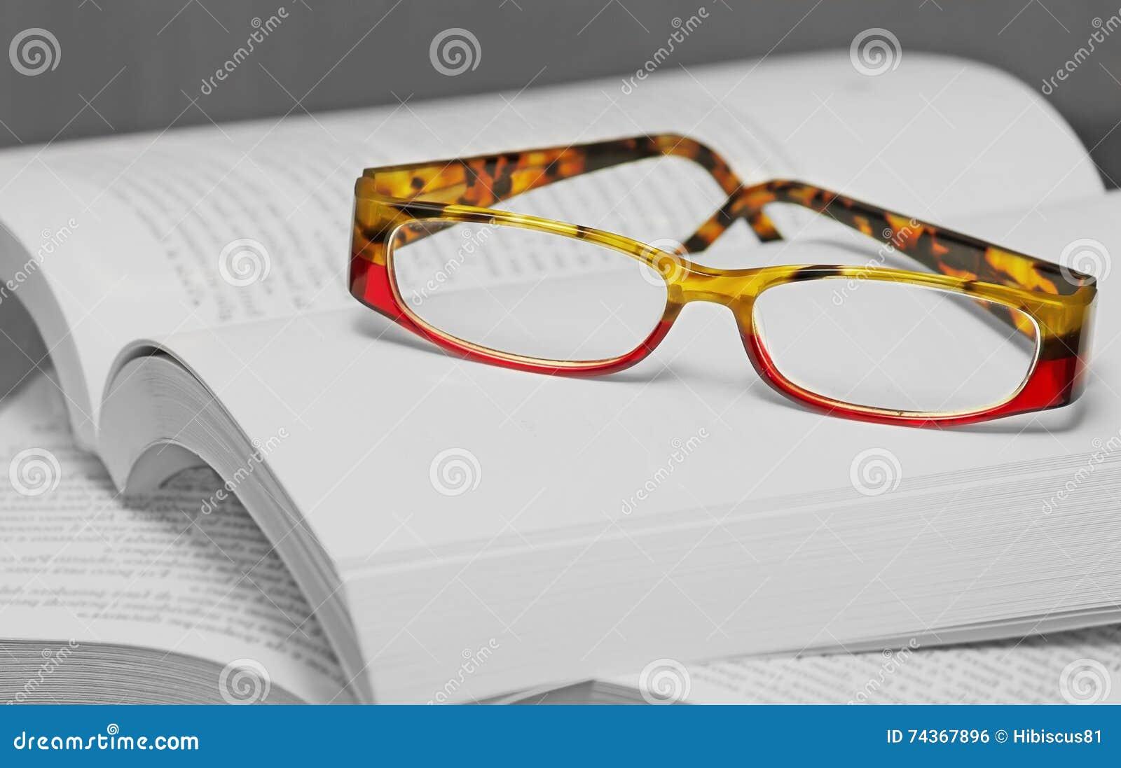 Eyglasses en una pila de libros