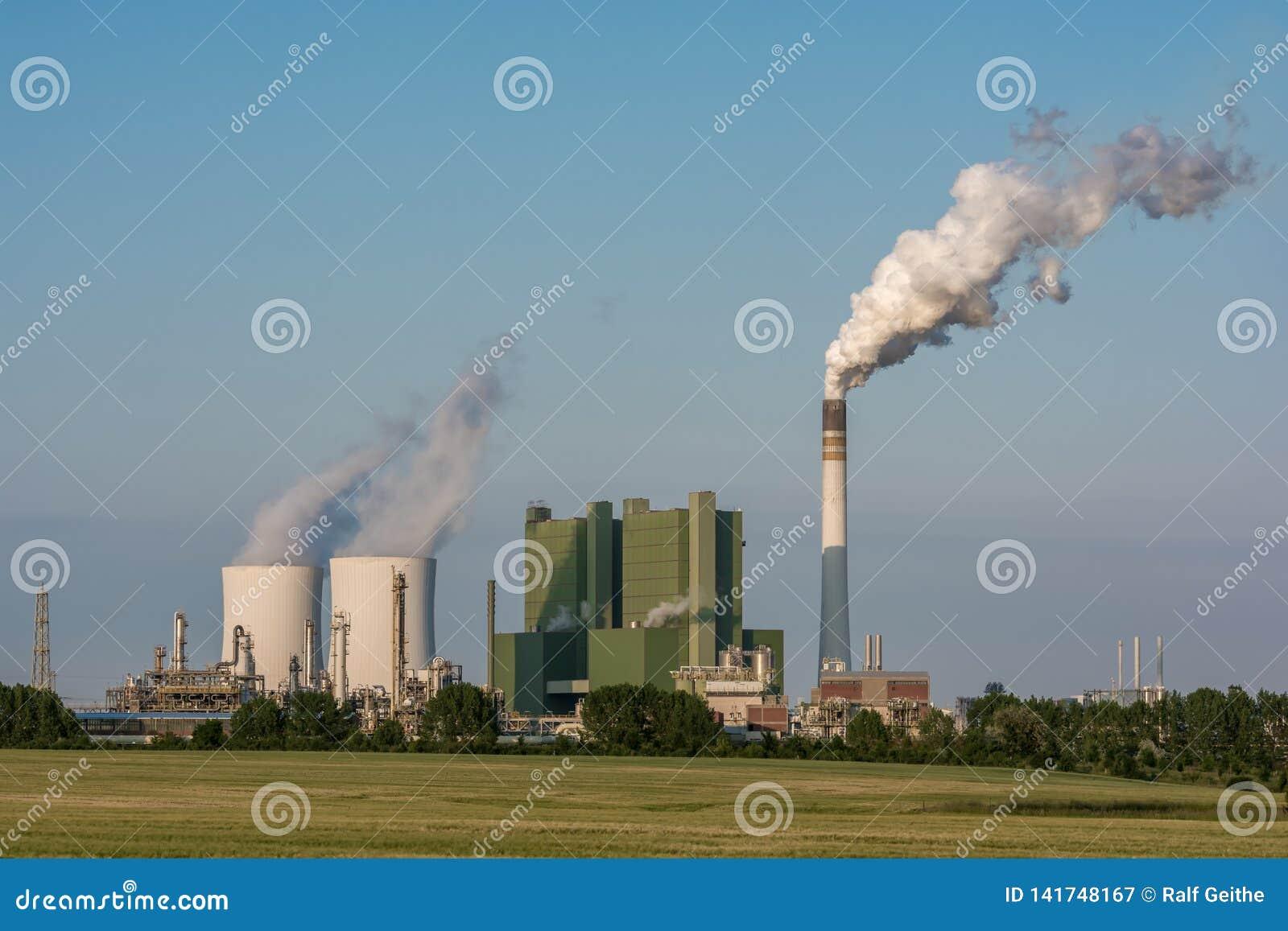 Fábrica grande con el cocido al vapor de torres de enfriamiento al vapor y fumar la chimenea