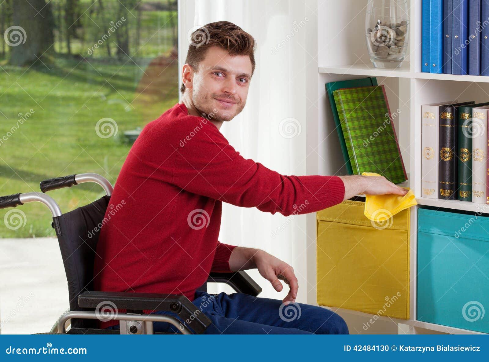 Fähig zu behindertem Mann wischt den Staub ab