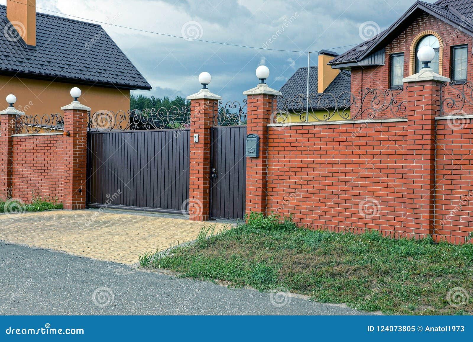 Fäktar den brunt järn stängda portar och delen av en lång tegelsten i gatan