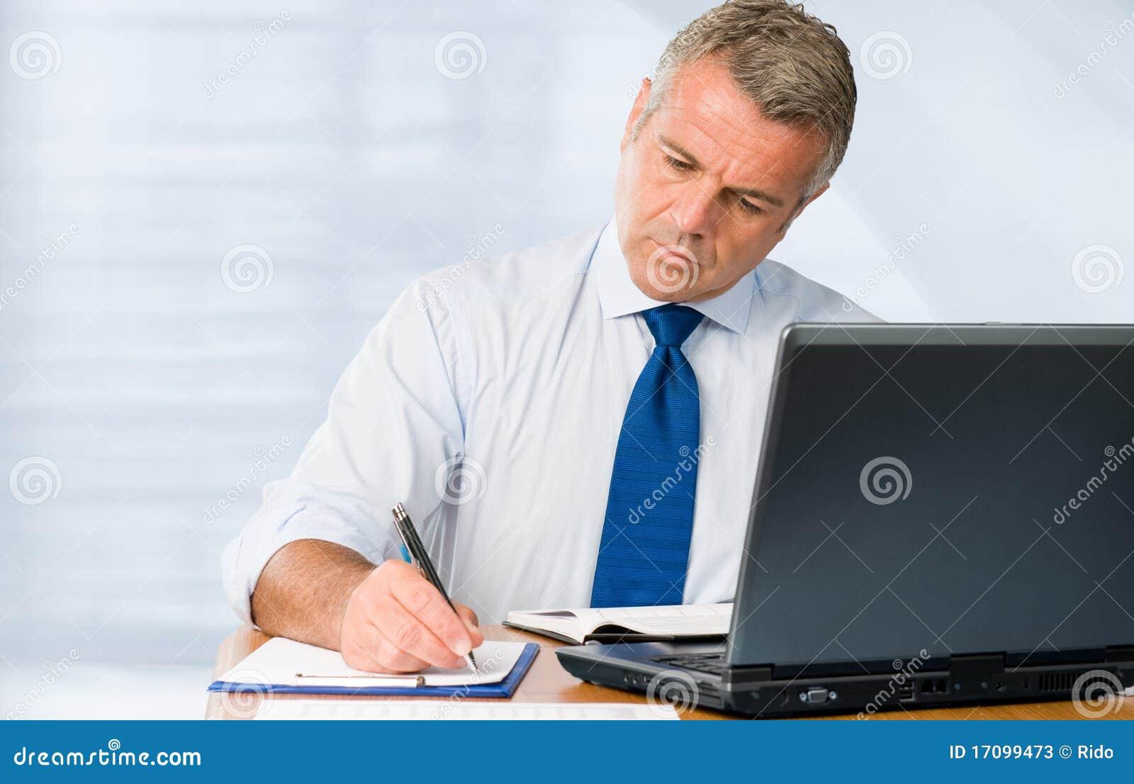 Fälliger Geschäftsmann, der im Büro arbeitet