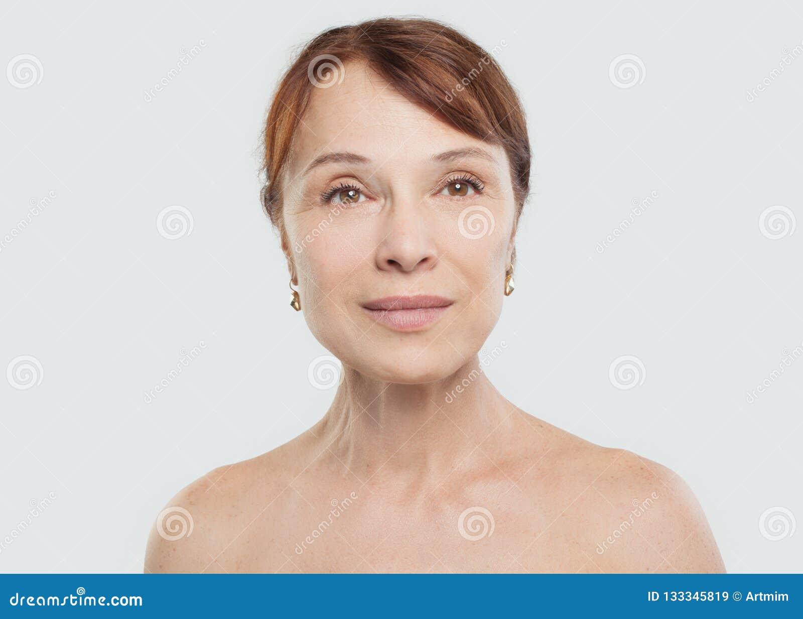 Fälliges Frauenlächeln Schönes mittleres erwachsenes weibliches Gesicht