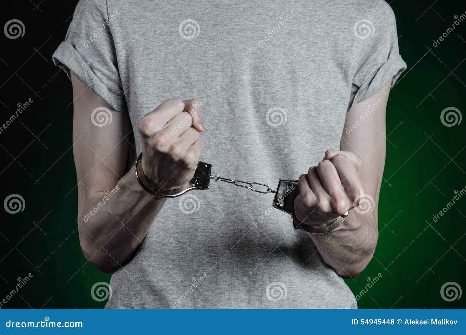 Fängelse och beslagit ämne: man med handbojor på hans händer i en grå T-tröja och jeans på ett mörker - grön bakgrund i stuen