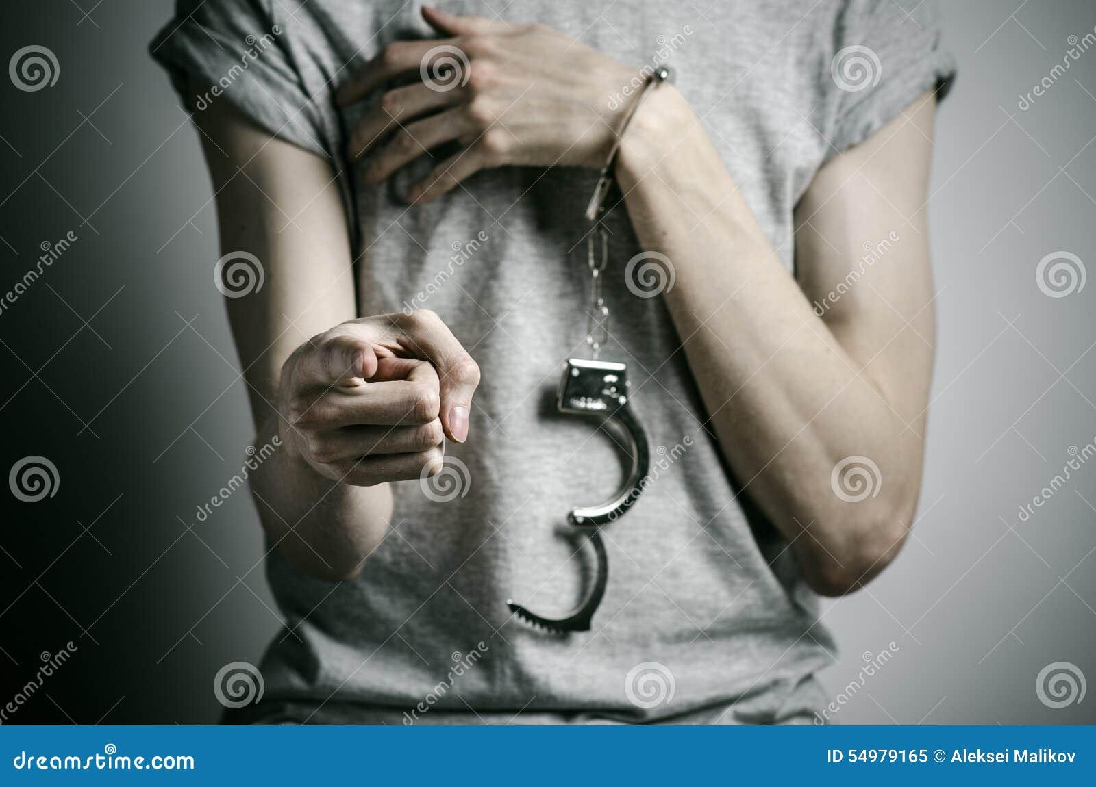 Fängelse och beslagit ämne: mannen med handbojor på hans händer i en grå T-tröja på en grå bakgrund i studion, satte på handbojor