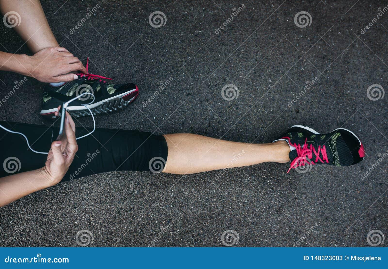 F?rdig idrottsman nenkvinnal?pare i sportswear som kopplar av, n?r utbildning med smartphonen