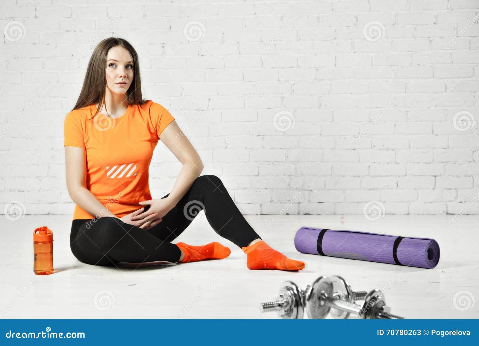 Färdig kvinna för sport som poserar i en idrottshall med utrustning, hanteln och det utbildande blocket
