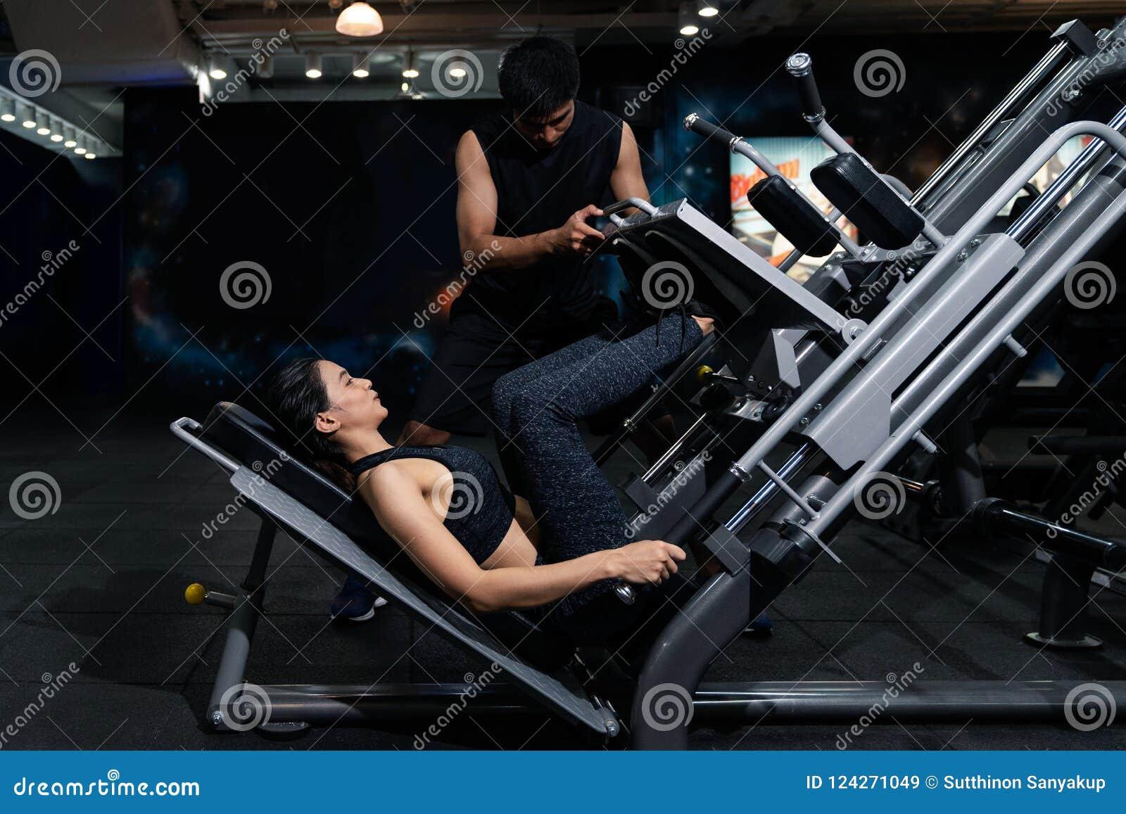 Färdig kvinna som utarbetar med instruktören på idrottshallen, kvinna som gör muskelutbildning på idrottshallen Idrottsman nen so