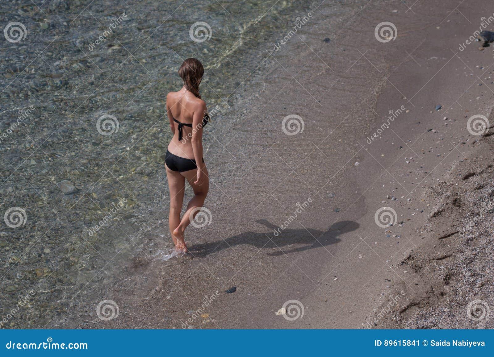 Färdig ung kvinnlig bärande svart bikini som går vid stranden