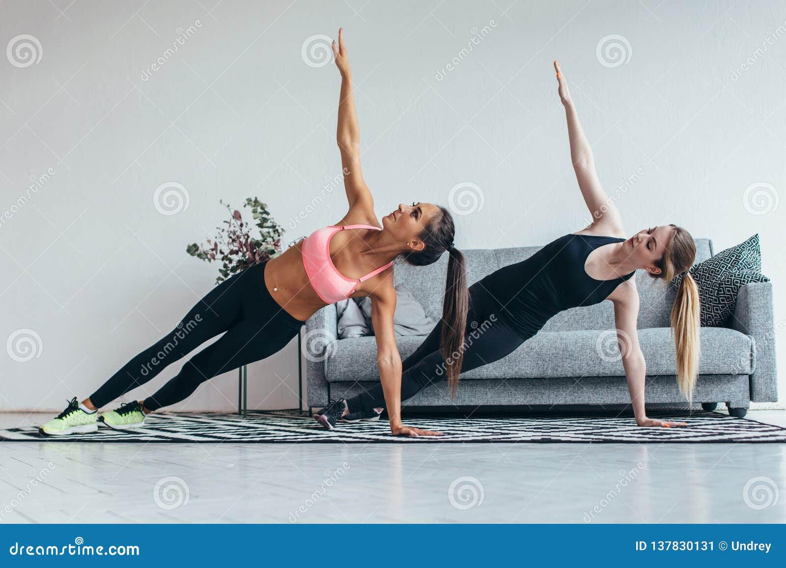 Färdiga kvinnor som gör sidoplankan, övar praktiserande pilates hemma
