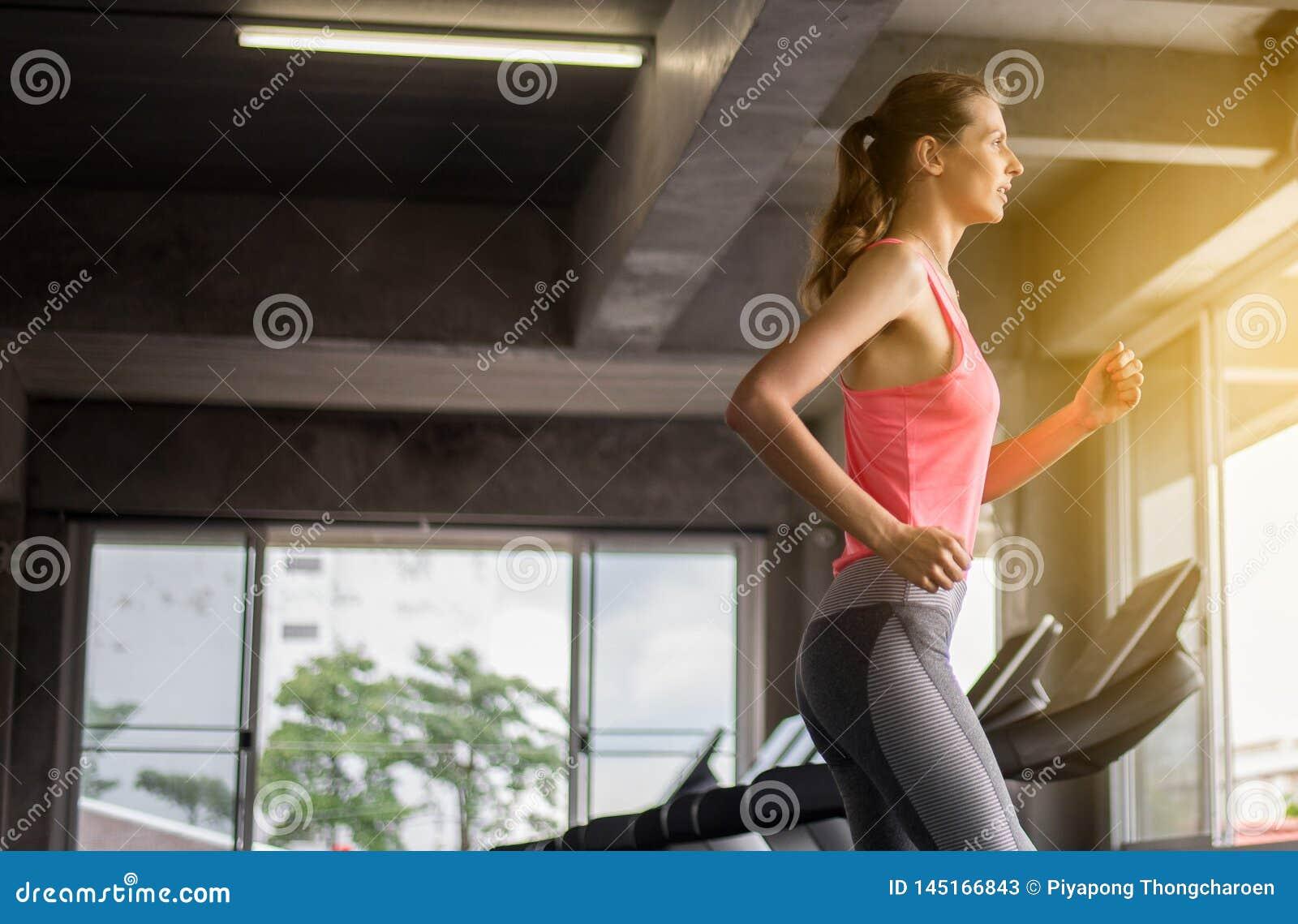F?rdiga kvinnor som k?r p? trampkvarnar som g?r cardio utbildning i en idrottshall, sunt livsstilbegrepp
