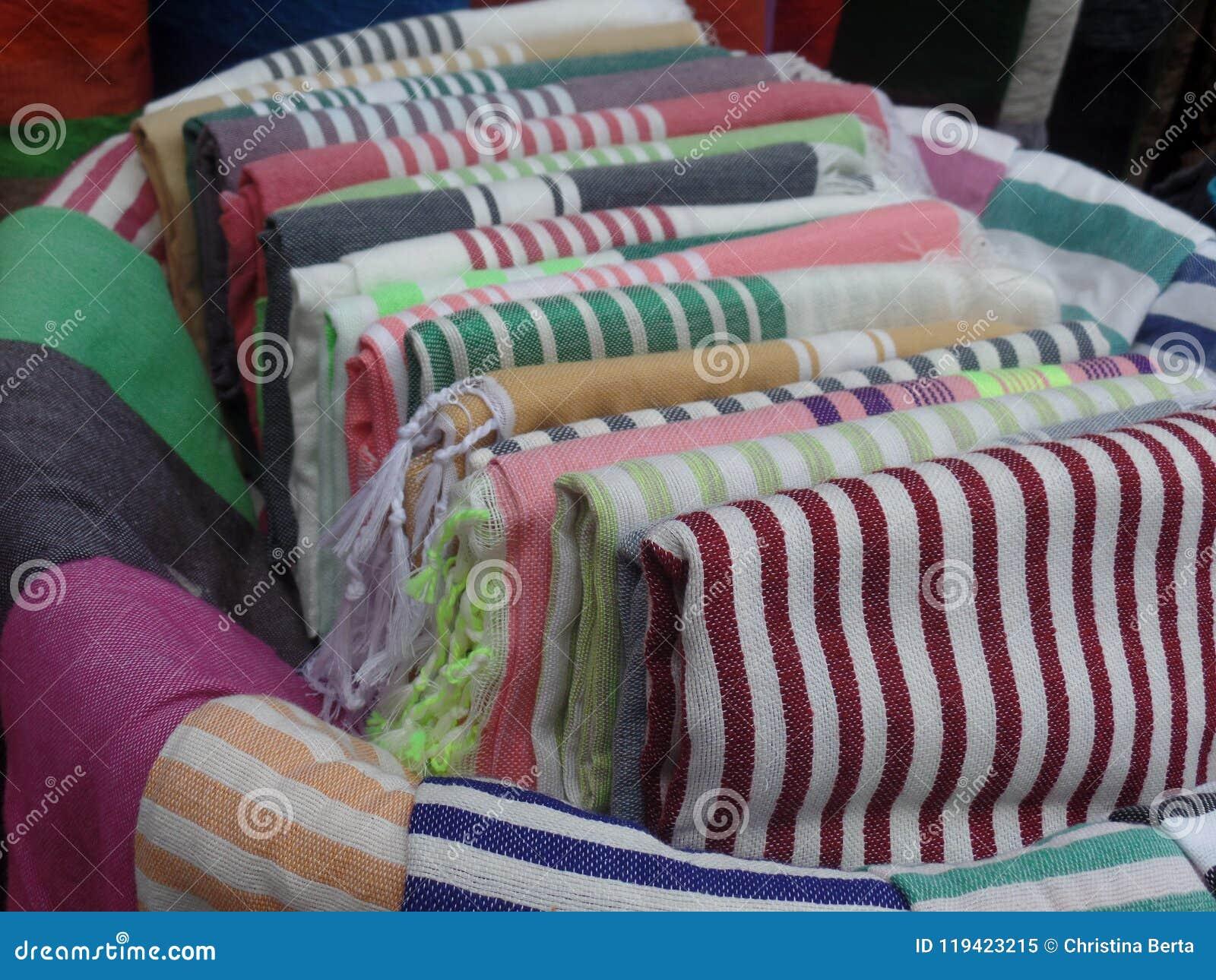 Färgade textiler som är till salu utanför en shoppa i Essaouira, Marocko