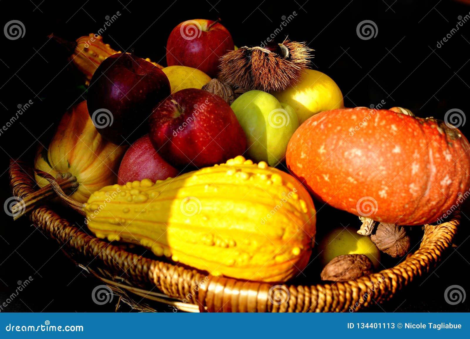 Färgglade äpplen, muttrar och pumpa i en träkorg som isoleras på svart bakgrund - höststilleben
