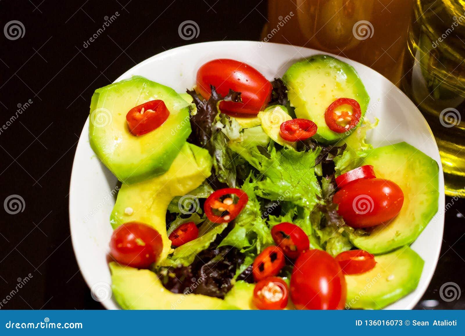 Färgglade sunda foods avokado, Olive Oil, äppelcidervinäger, Cherry Tomatoes, röda chili grönsallat, för sund matvana