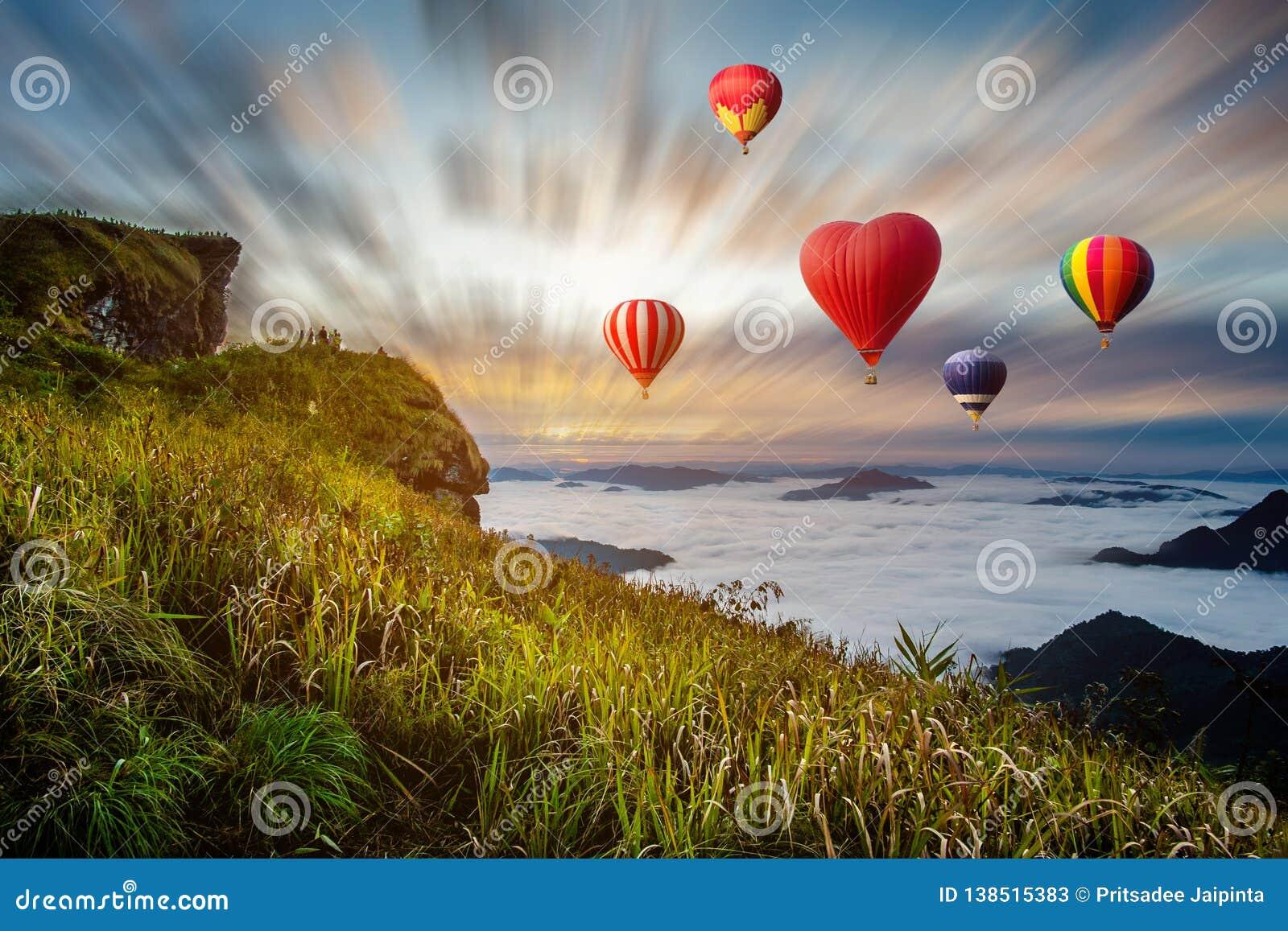 Färgglade varmluftsballonger som flyger över berget