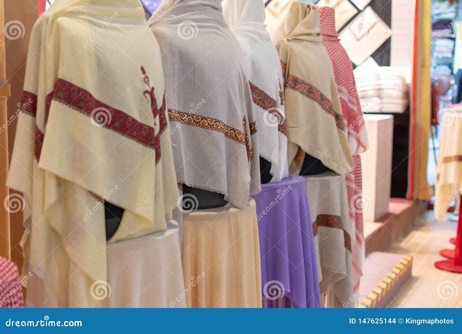 Färgglade vita manliga dishdashhuvudhalsdukar ställer upp till salu in på marknaden för den globala byn i Dubai, Förenade Arabemi