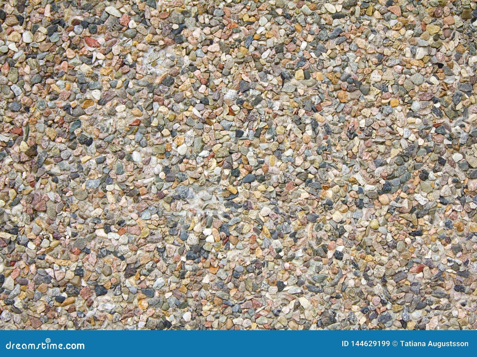 Färgrik abstrakt bakgrund av små kiselstenar och stenen inbäddade i cement