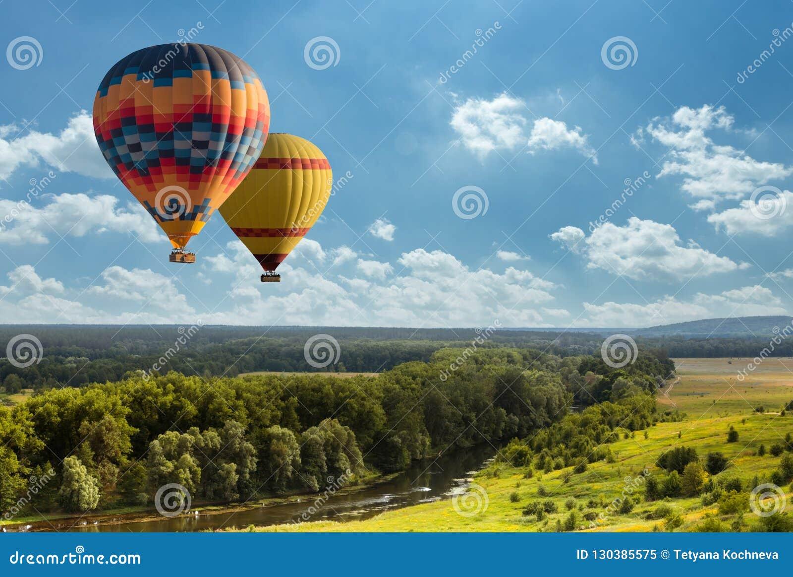 Färgrik ballong för varm luft som flyger över grönt fält