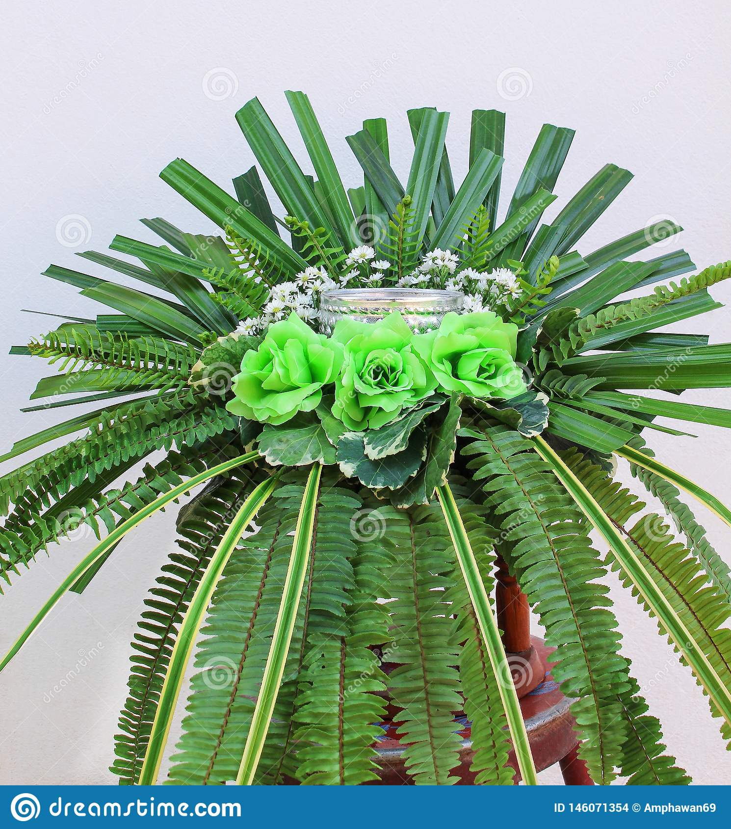 Färgrik bukettgräsplan för konstgjorda blommor steg, ormbunkesidor och gömma i handflatan på vit betongväggbakgrund
