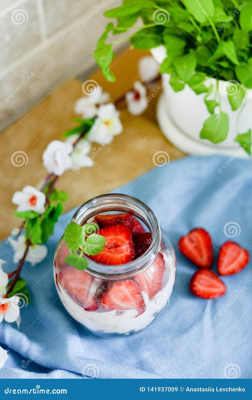 Färgrik fruktsallad i en krus på vit och blå lantlig träbakgrund Top beskådar Jordgubbemilkshake i krus