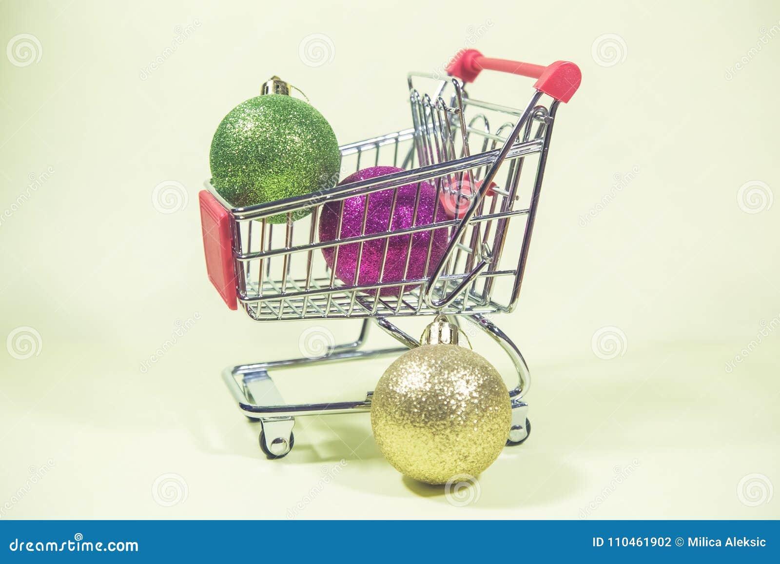 Färgrik jul klumpa ihop sig i den lilla metallshoppingvagnen på