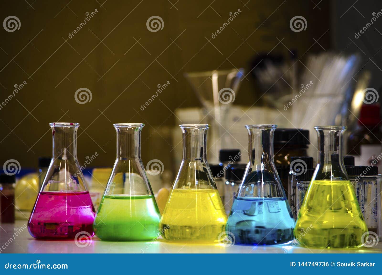 Färgrik lösning i den koniska flaskan som fodras på en bänk i en kemilabb med experiment för organisk kemi för suddighetsbakgrund