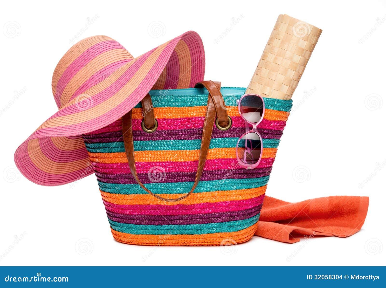 Färgrik randig strandpåse med handduk och sunglass för hattsol en matt
