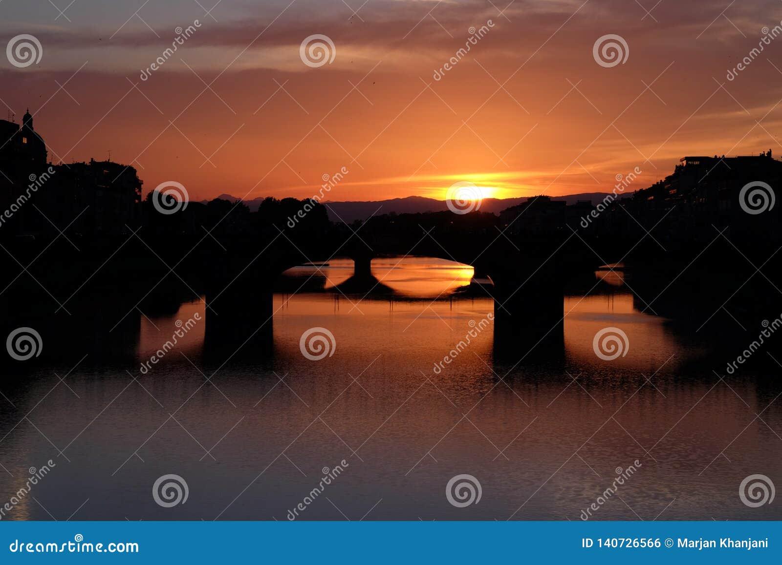 Färgrik solnedgångsikt från den Arno floden i Florence, Italien