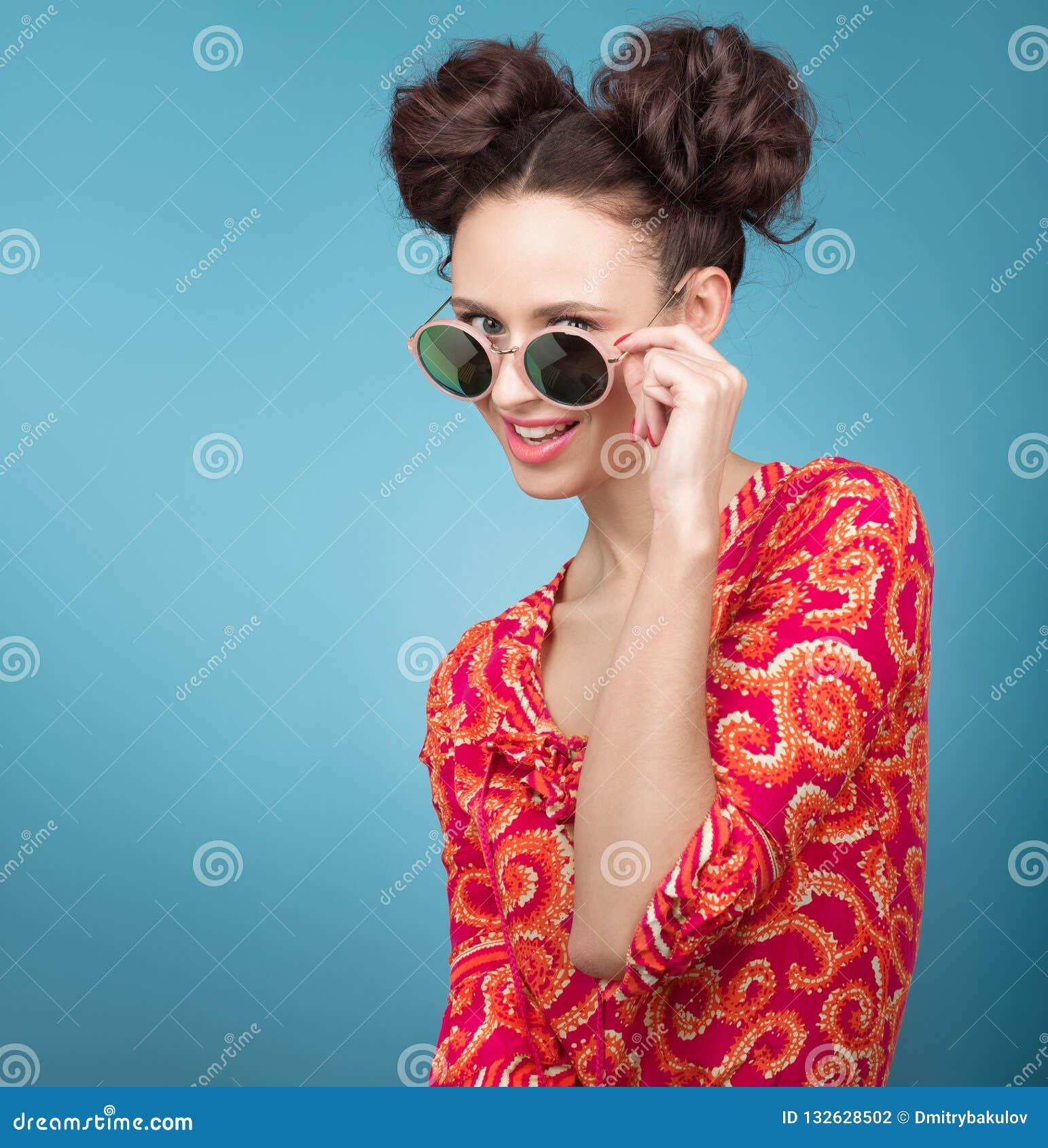 Färgrik studiostående av den härliga unga kvinnan som poserar i solglasögon En stilfull frisyr