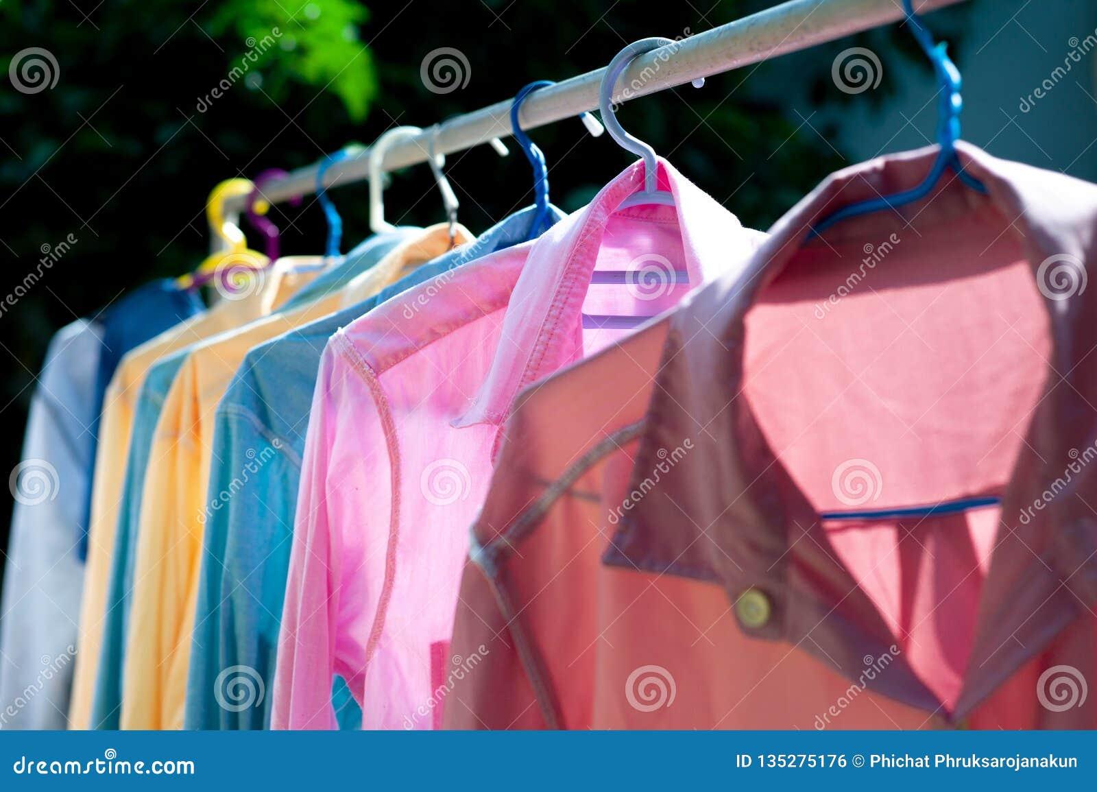 Färgrik våt kläder som hänger på stålklädstrecket för att torka vid värmen av solen