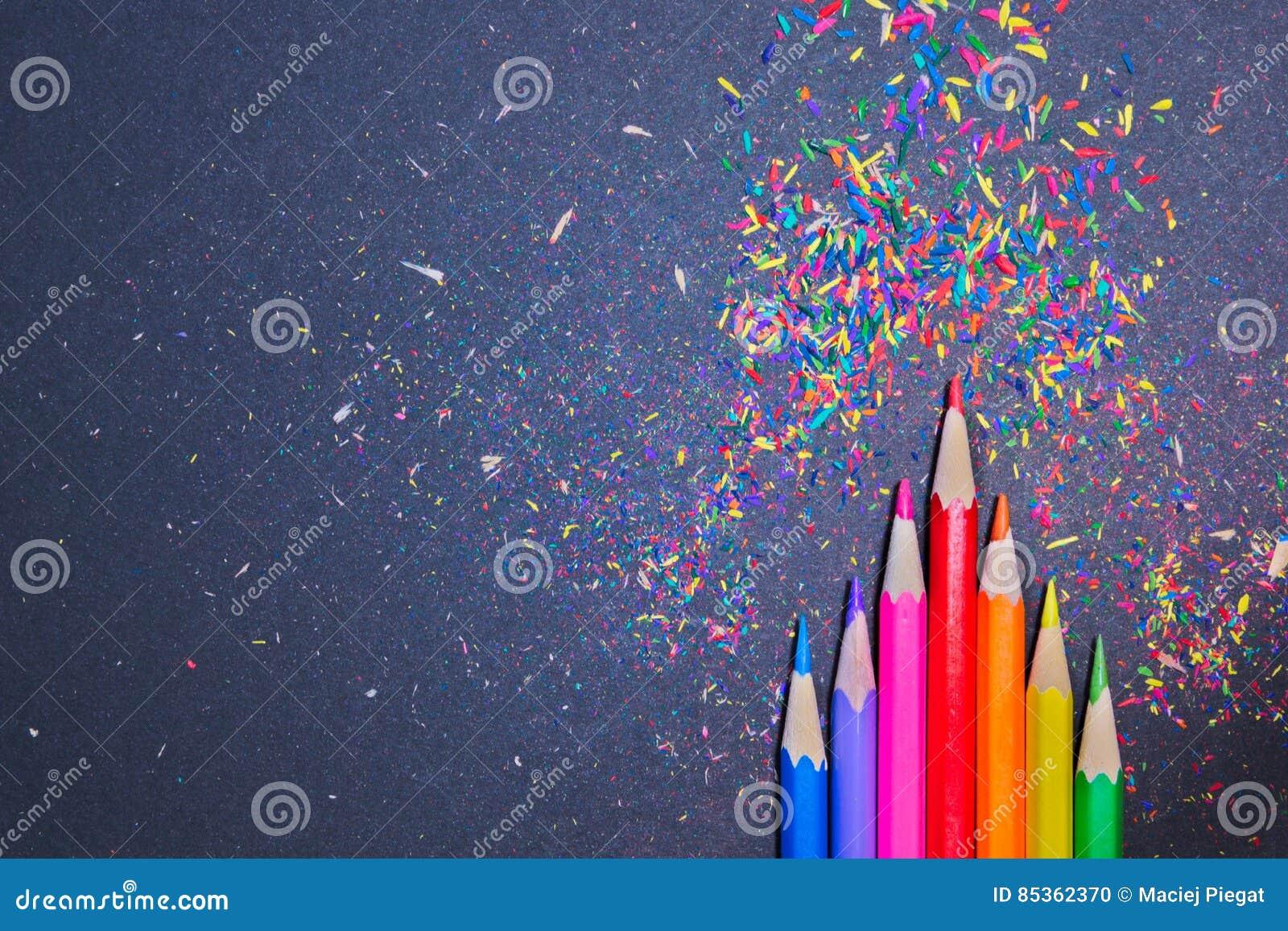 Färgrika blyertspennor med färgrika shavings på en svart bakgrund