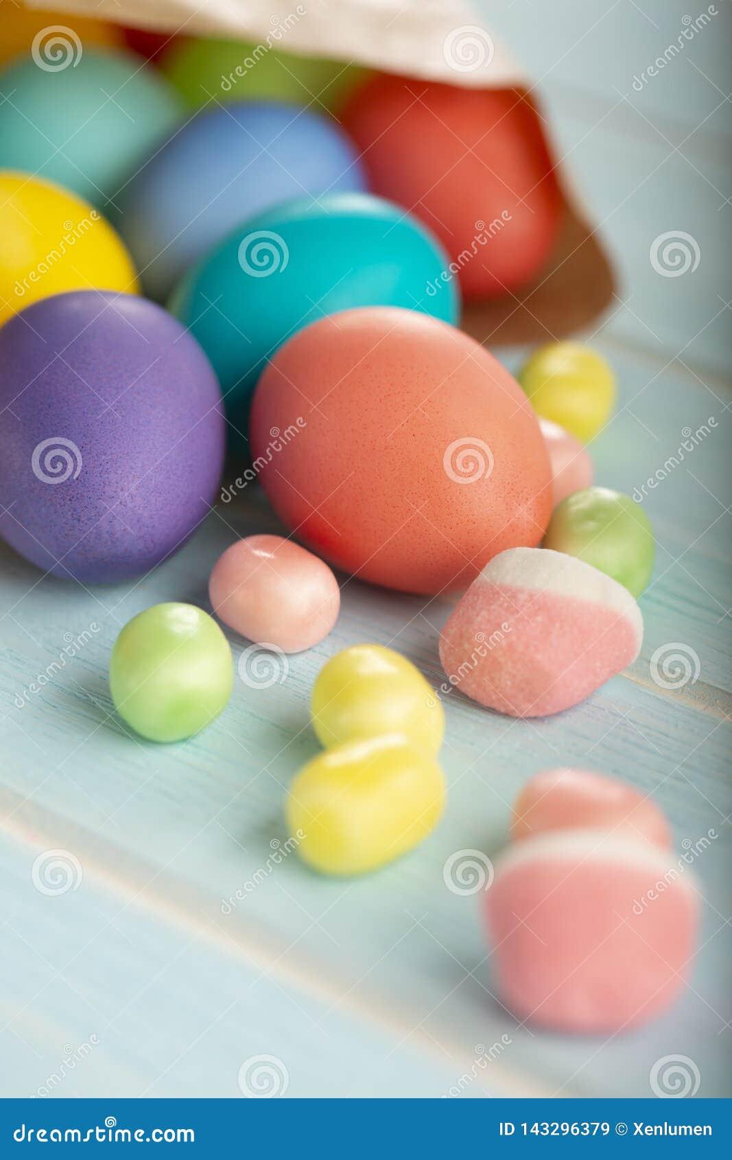 Färgrika färgade fega ägg för påsk i en pappers- påse och sötsaker