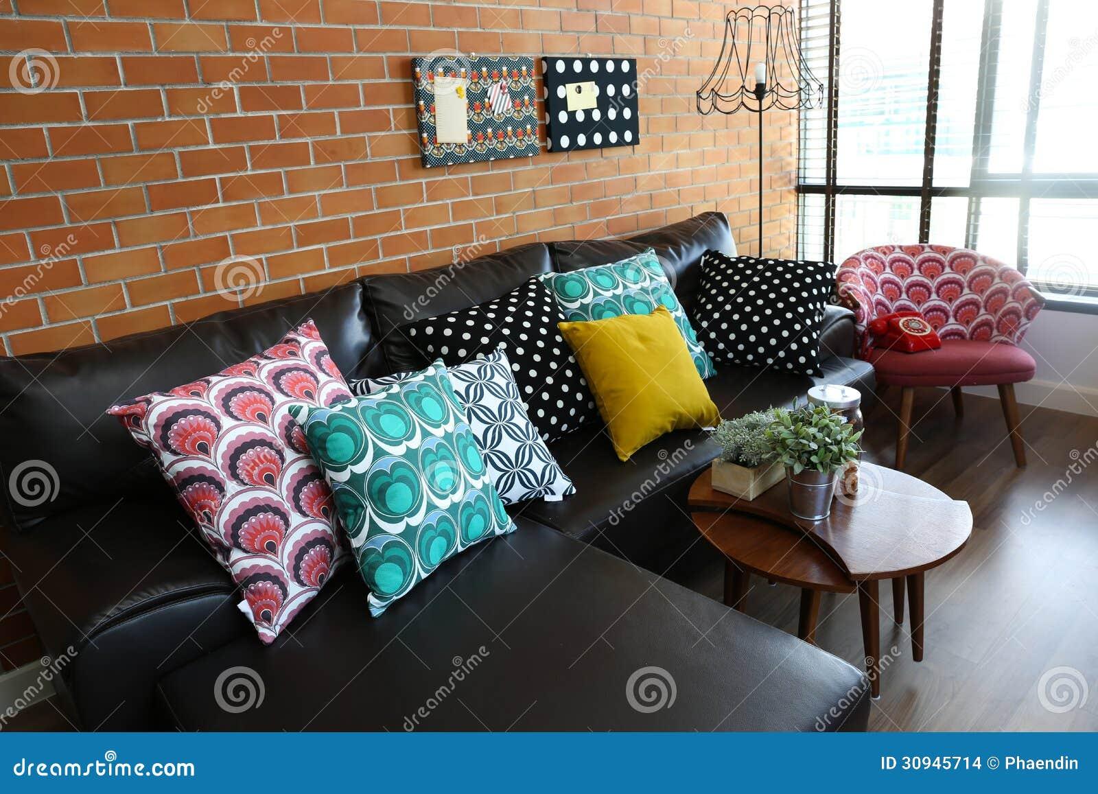Färgrika kuddar på en soffa med tegelstenväggen